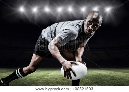 Determined sportsman looking away while playing rugby against rugby pitch