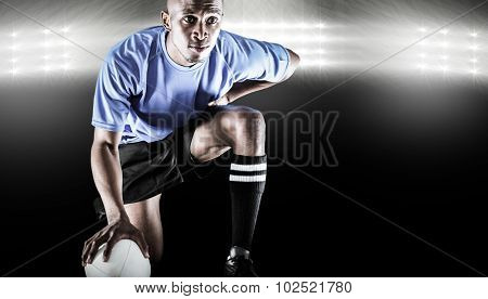Serious rugby player kneeling while holding ball against spotlight