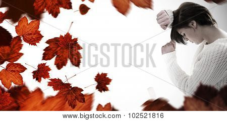 Sad pretty brunette leaning against wall against autumn leaves