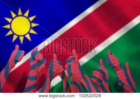 Group of hands giving thumbs up against namibian flag on white background