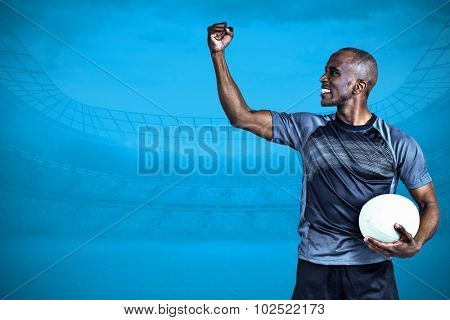 Sportsman with clenched fist after victory against blue background with vignette