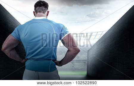 Rugby player with hands on hips against rugby stadium