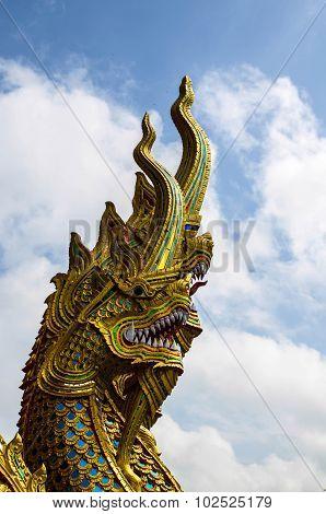 Golden Naga Statue with blue sky