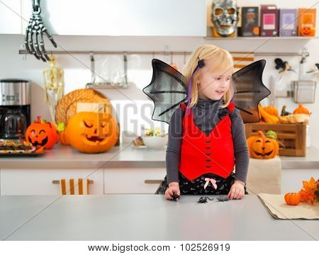 Funny Girl In Halloween Bat Costume In Decorated Kitchen
