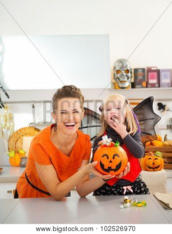 Happy Mother With Daughter In Bat Costume Eating Halloween Candy
