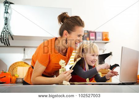 Happy Mother With Halloween Dressed Daughter Having Video Chat