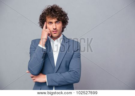 Portrait of a pensive businessman looking at camera over gray background
