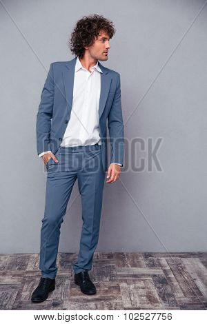 Full length portrait of a thoughtful businessman looking away on gray background