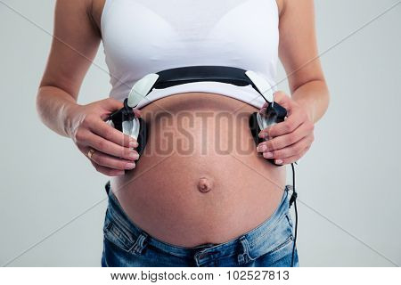 Pregnant woman holding headphones on belly isolated on a white background