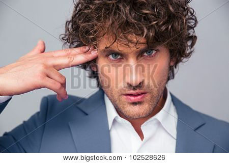Portrait of a serious businessman doing gun gesture at head over gray background