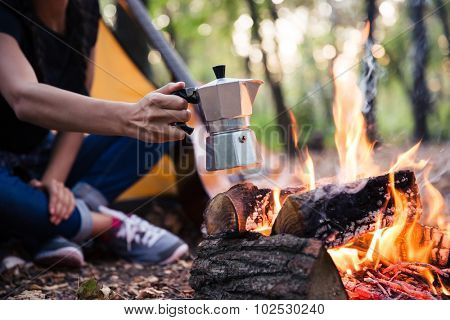 Portrait of a couple making coffee on the bonfire in the forest