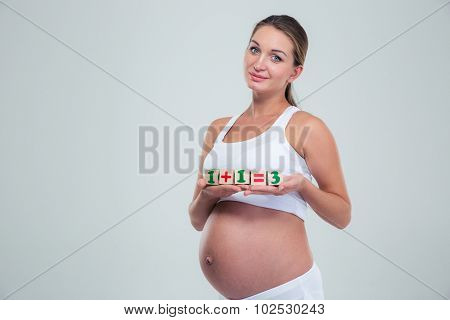 Pregnant woman holding bricks with equation 1 + 1 = 3 isolated on a white background