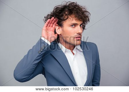 Portrait of a handsome business?an making eavesdropping gesture over gray background
