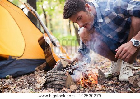 Man and bonfire in autumn forest