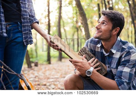 Portrait of a woman giving to man firewood outdoors