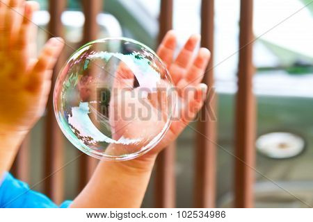 Soap Bubbles Are Floating Through In Hand Of The Little Children.
