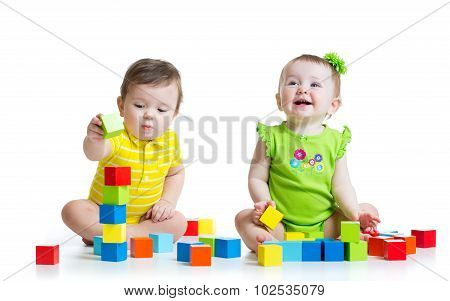 Two adorable kids playing with toys. Toddlers girl and boy sitting on floor. Isolated on white backg