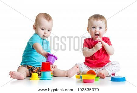 Cute babies playing with color toys. Children girl and boy sitting on floor. Isolated on white backg