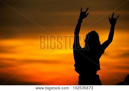 Silhouette of  girl show hands love sign