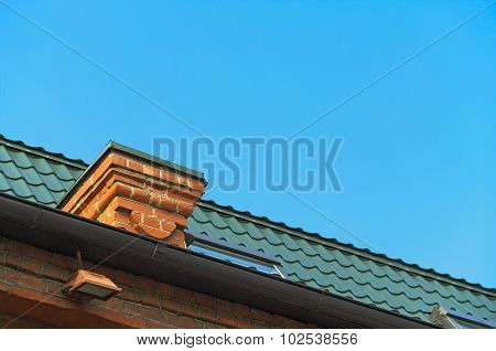 Detail Of The Roof With Chimneys Against The Blue Sky