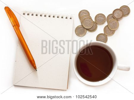 A spiral notebook with a place for text, a pen, a cup of tea and a euro coins on white background