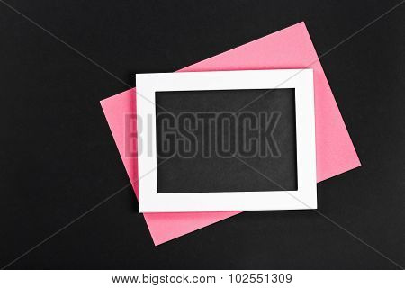Horizontal White Photo Frame With Black Field And Pink Paper Under Angle On Black Background Isolate
