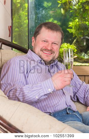Man sitting in armchair with glass of champaign with aquarium on background