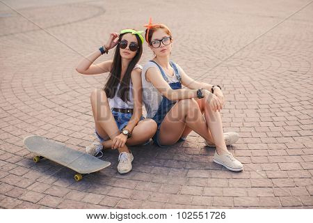Two beautiful young girls on a skateboard in the city.
