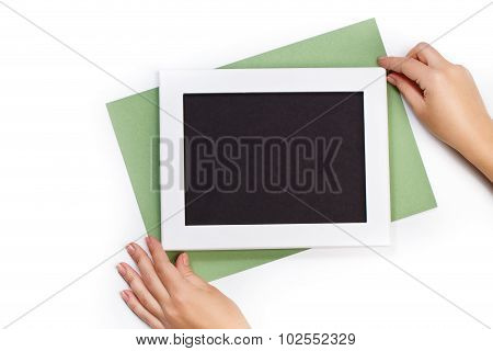 Hands Holding Horizontal White Photo Frame With Black Field And Green Paper Under Angle On White Bac