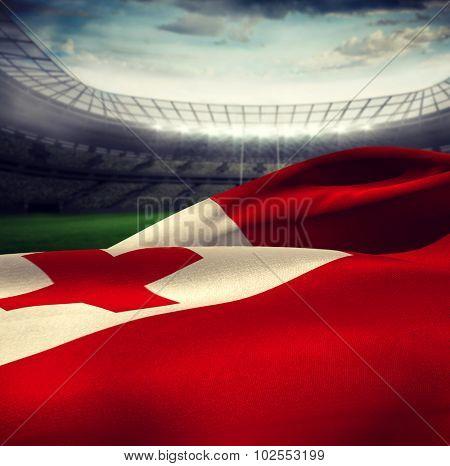 Waving Tonga flag against rugby stadium