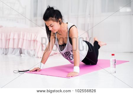 Fit sporty woman in headphones doing push ups home training listening music at smartphone concept cr