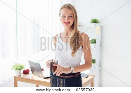 Portait of beautiful successful business woman holding cup coffee looking at camera