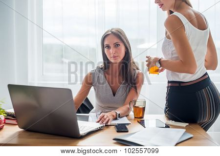 Young businesswoman sitting at desk front laptop computer with her coleague. Coffee break office
