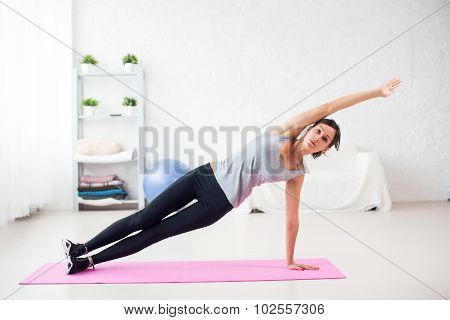 Fit woman doing side plank yoga pose at home in the living room on mat Concept pilates fitness healt