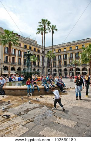 BARCELONA, SPAIN - MAY 02: Groups of Tourists Gathered Around Central Water Fountain in Placa Reial, a Popular Tourist Destination in Barcelona, Spain
