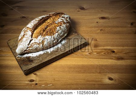 Loaf of bread on brown wooden cutting board
