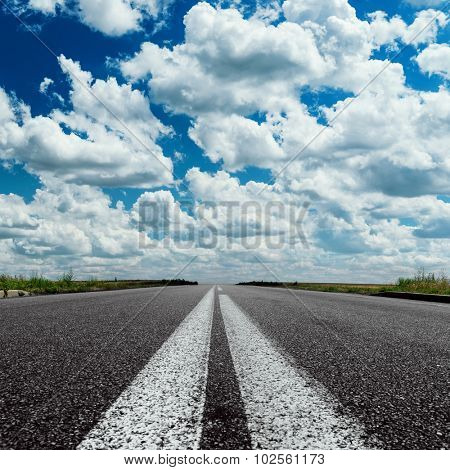 dramatic sky over asphalt road with two white line