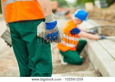 Worker Holding Cobblestones