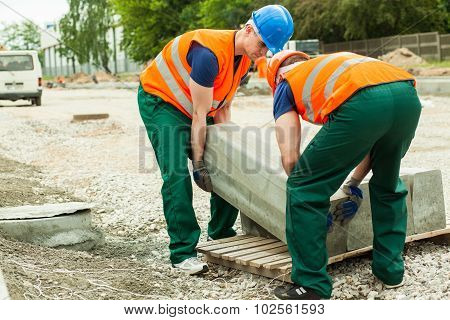 Workers Heaving Block Of Setts