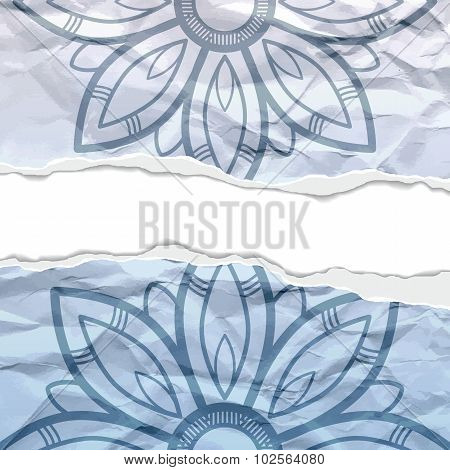 Background of crumpled torn paper with floral circular pattern.