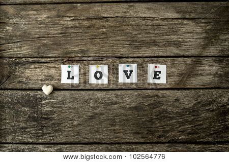 Word Love Spelled With Individual White Cards Pinned To A Textured Rustic Wooden Boards