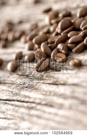Coffee Beans Sprinkled On A Textured Rustic Wooden Boards