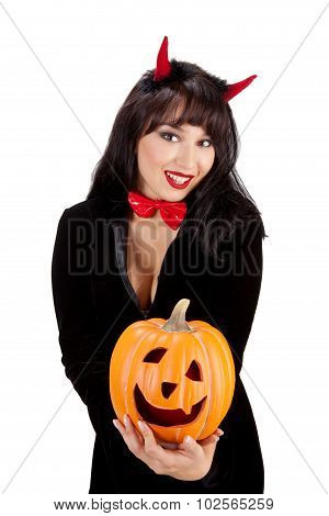 Young Woman Holding Jack O'lantern In Costume Of Black Devil On A White Background