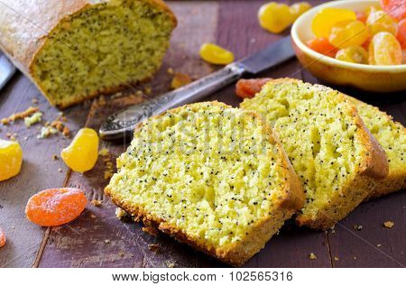 cake with kumquats and poppy seed on wooden background