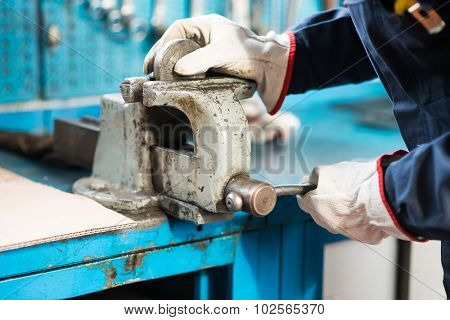 Close-up of a worker securing a metal plate in a vise