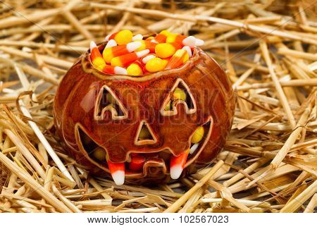 Spooky Pumpkin Filled With Candy Corn On Straw
