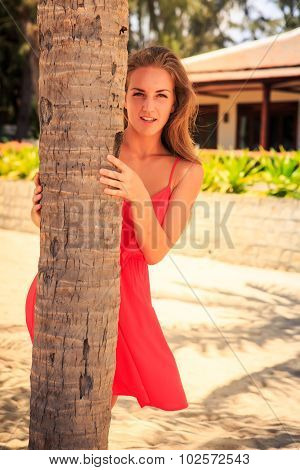 Blond Girl In Red Leans Out Of Palm Looks Into Camera