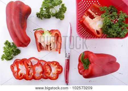 Red Capsicum Peppers On White Wood Table.