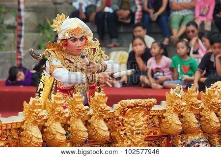 Balinese Man Dancing And Playing Music On Gamelan Gong