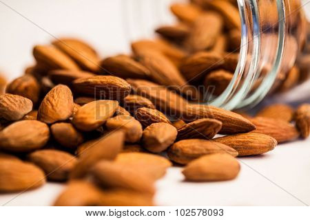 Cropped image of almonds spilling out of a jar on the table